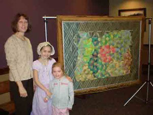 The little girl representing early Oregon settlers, her little sister, and me pose next to the quilt.