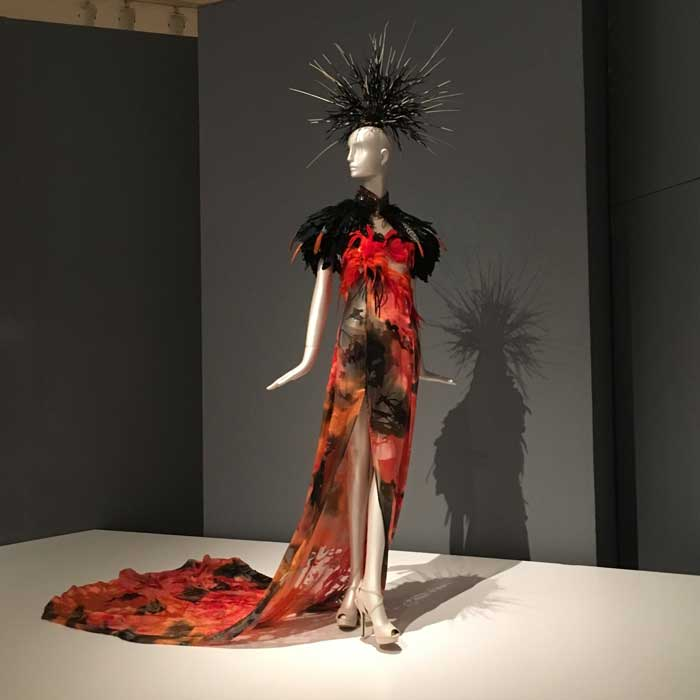 Artist: Orlando Dugi Desert Heat Collection Dress: Dyed silk, organza, feathers, beads, 24-karat gold Cape: feathers, beads, silver Headpiece: African porcupine quills, feathers