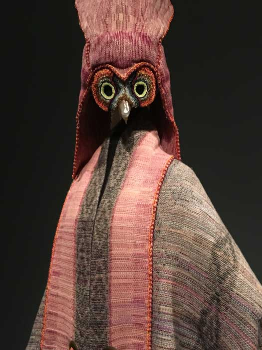 "Artist: Margaret Roach Wheeler ""The Messenger (The Owl)"" Cape: silk-wool yarn Headpiece: silk-wool yarn, metal, silver, glass beads and peacock feathers"